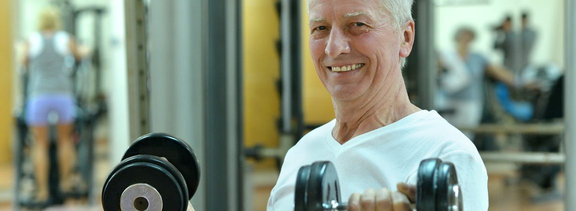 Older man lifting weights in a gym
